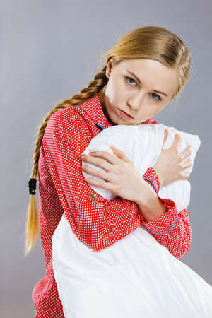 Mental health depression insomia concept. Sad depressive young woman teen blonde girl wearing red pajamas sitting on bed embracing pillow, on grey wall background Stock Photo