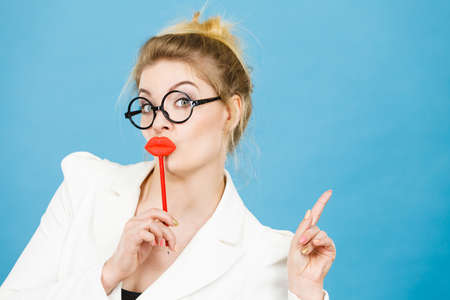 Lovely sweet business woman elegant clothing nerdy glasses holding red fake lips on stick having fun, pointing up with finger at copy space, on blue. Carnival funny accessories concept.
