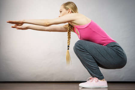 Woman training, working out at home doing sit ups squats, being fit and healthy. Stock Photo