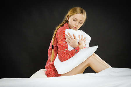 Mental health depression insomia concept. Sad depressive young woman teen blonde girl wearing red pajamas sitting on bed embracing pillow, on dark black night background