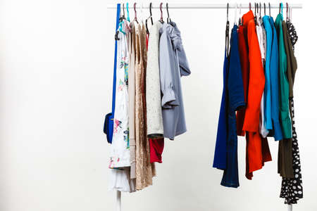 Wardrobe furniture concept. Many clothes on hangers in closet. Studio shot on grey background. Stockfoto