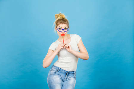 Crazy woman casual style nerdy glasses holding red fake lips on stick having fun, on blue. Photo take and carnival funny accessories concept.