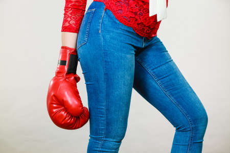 Unrecognizable woman wearing red boxing glove, and tight blue jeans. Grey background.