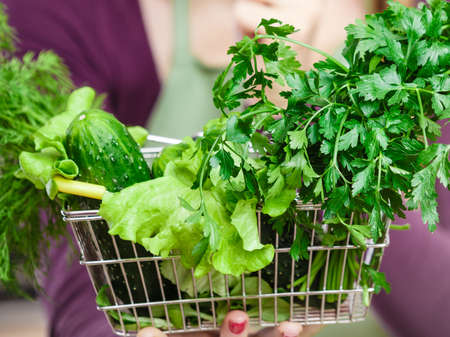 Buying healthy dieting food concept. Woman in kitchen having many green vegetables holding small shopping basket.