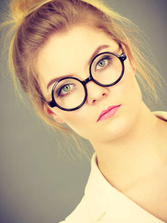 Bored focused or grumpy blonde college teacher or office orker woman wearing nerdy eyeglasses, white jacket. Stock Photo