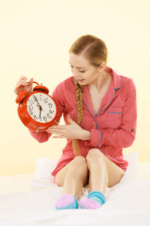 Sleepy young woman wearing cute pink pajamas holding big red old fashioned clock showing sleep time.