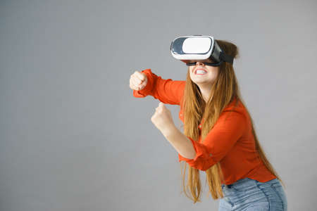 Young emotional woman wearing virtual reality goggles headset, vr box. Connection, technology, new generation and progress concept. Studio shot on gray