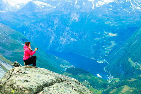 Tourism vacation and travel. Female tourist taking photo with camera, enjoying Geiranger fjord and mountains landscape from Dalsnibba Plateau viewpoint, Norway Scandinavia. Stock Photo