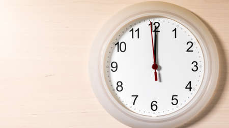 Clock hanging on wall ticking showing twelve hours 版權商用圖片
