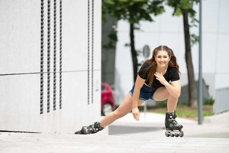 Woman wearing roller skates riding in town. Female being sporty stretching her legs before long ride.