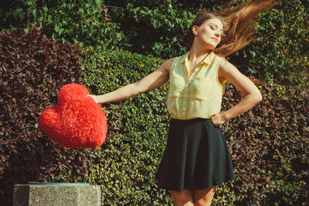 Love romance heartbreak sadness concept. Girl throwing heart into dumpster. Young lady holding plush love symbol over bin. 스톡 콘텐츠