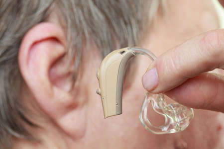 Closeup senior woman with hearing aid in her ear. Health care, hear amplify, device for the deaf. Stock Photo