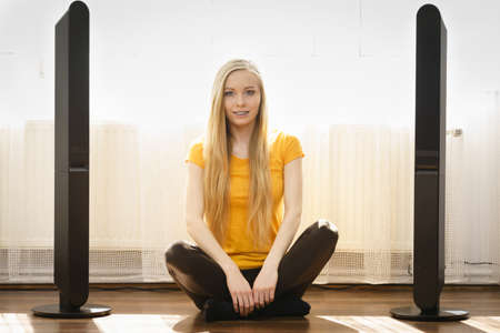 Happy young woman with long blonde hair sitting next to speakers. Home cinema theatre equipment.