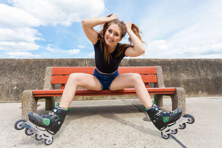 Happy smiling young woman wearing roller skates outdoor. Girl having fun resting on bench.