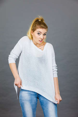 Woman wearing too big jumper, not fitting after weight loss. Grey background Stock Photo