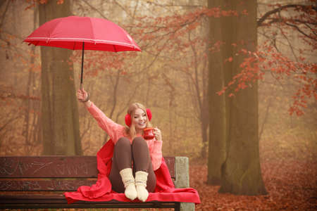 Happiness carefree and fall concept. Joyful woman relaxing in autumn park on bench under umbrella enjoying hot drink holding mug with warm beverage. Orange leaves background Stock Photo