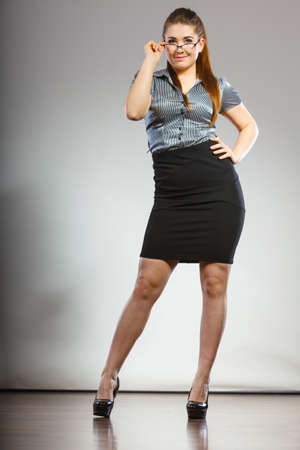 Teacher looking elegant woman wearing dark tight skirt, high heels, shirt and eyeglasses.