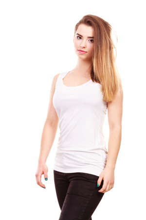 Teenage beauty concept. Portrait of young teenager woman with long brown having neutral face expression, wearing white tank top and black leggings Stock Photo