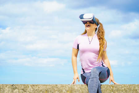 Young woman testing VR glasses outside. Female wearing virtual reality headset during summer weather