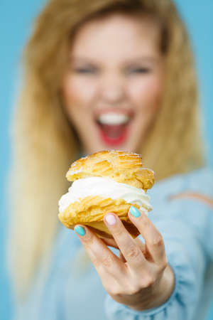Sweet food and happiness concept. Funny joyful blonde woman holding yummy choux puff cake with whipped cream, excited face expression. On blue Stock Photo