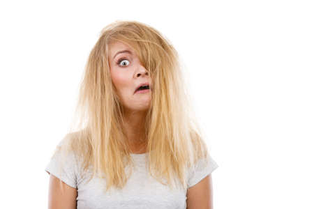 Bad hairstyle concept. Crazy, mad blonde woman with messy hair looking stressed out. Studio shot on white background. 版權商用圖片
