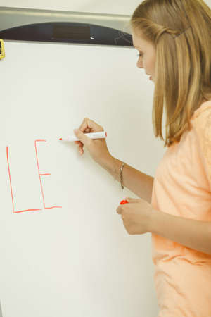 Education, knowledge, wisdom and learn new things concept - student girl writing Learning word on whiteboard inviting to join Stock Photo