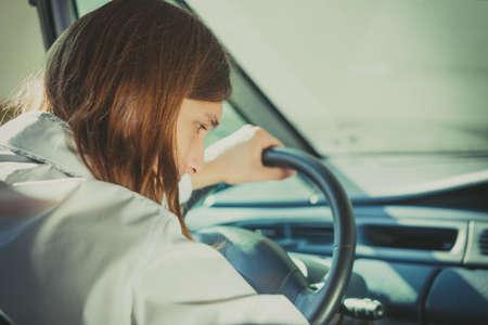 Young man driver wearing white shirt having long hair, driving car carefully. Stock Photo