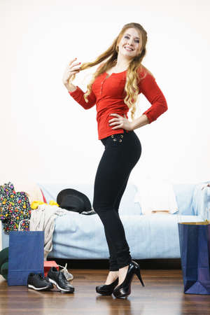 Happy cheerful woman presenting fashionable outfit. Female wearing black high heels, dark skinny trousers and red top.
