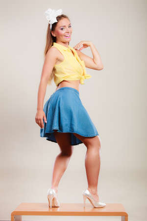 Alluring seductive pretty pin up girl wearing hairband bow, skirt and high heels. Attractive gorgeous young retro woman dancing on table. Foto de archivo