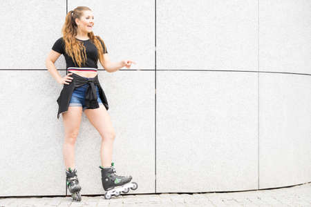 Happy joyful young woman wearing roller skates riding in town. Female being sporty having fun during summer time.