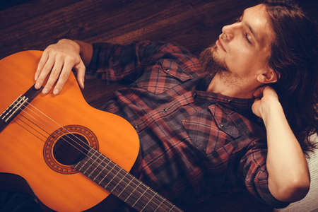 Music concept. Pensive man with guitar. Young male is lying on the floor with wooden instrument.  Stockfoto