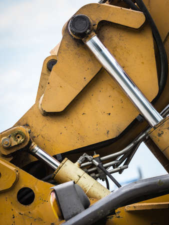 Pneumatic machine parts close up on details. Big industrial machinery outdoor. Industry loaders concept.