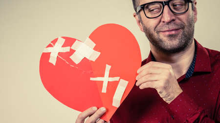 Healed love. Valentines Day concept. Adult smiling man holding big red heart with plaster. Male healing relationship. Standard-Bild