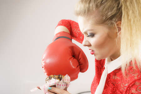 Dieting, weight loss concept. Funny blonde woman holding yummy chocolate cupcake cake and boxing glove, fighting off bad food. On grey