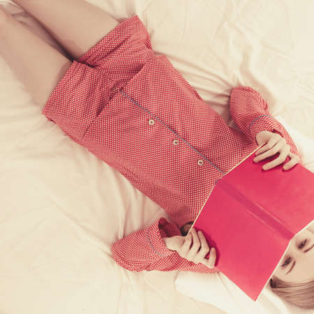 Girl lying in bed reading book. Young female wearing red dotted pajamas relaxing at home on mattress.