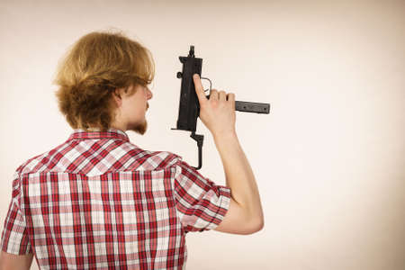 Young unrecognizable man standing backwards holding gun. Private weapon, security service and safety concept. Stock Photo