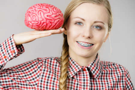 Intellectual expressions, being focused concept. Closeup of attractive woman happy thinking face expression holding brain Stock Photo