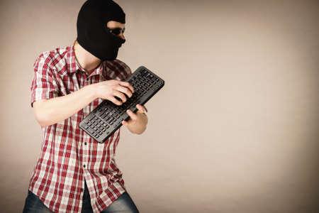 Crazy hacker man. Unrecognizable guy wearing black balaclava holding computer keyboard. Hate speech on the internet. Stock Photo