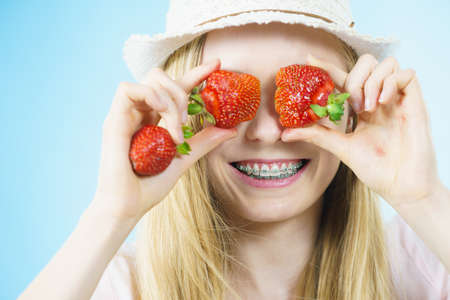Young positive woman playing with fresh strawberries fruits, on blue. Healthy meal. Stock Photo