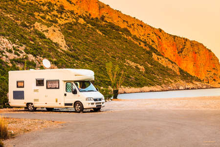 Tourism vacation and travel. Camper van on beach sea shore in summer time, Greece Standard-Bild