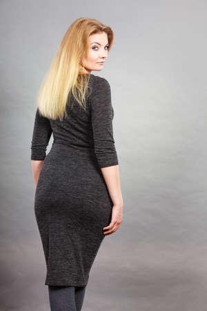 Woman wearing tight black dress showing her feminine body shape, back view.