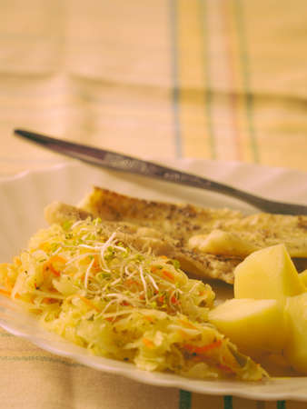 Food. Ready delicious dinner fish meat with salad and potatoes on kitchen home table. Meal time. Indoor. Stock Photo