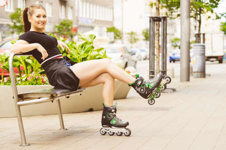 Happy joyful young woman wearing roller skates sitting in town. Female being sporty having fun during summer time.