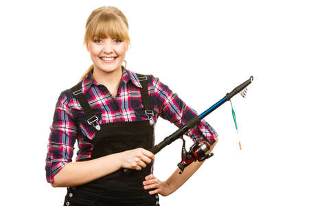Fishing concept. Attractive woman in dungarees, pink check shirt holding rod. Isolated background Banque d'images