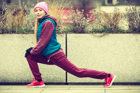 Sport and recreation. Fit slim sporty teen girl stretching warming up outdoor on city street. Woman exercising on fresh air.
