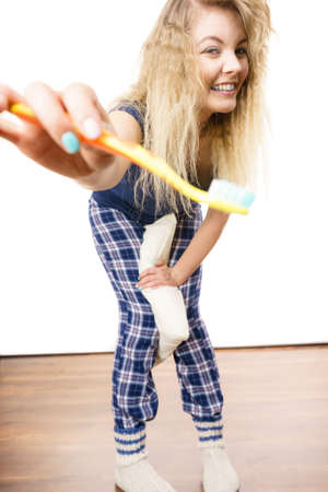 Happy woman brushing her teeth. Having fun during morning routine concept. Indoor shot.