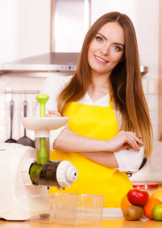 Woman young housewife in kitchen with fruits and juicer preparing to make fresh juice. Healthy eating, cooking, vegetarian food, dieting and people concept Stock Photo