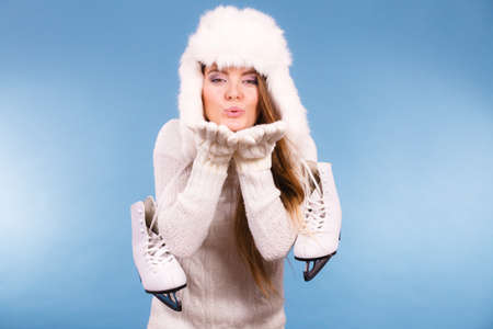 Winter sport activity concept. Atractive girl making kiss gesture wearing warm clothes, ice skates and furry hat, blue background studio shot.