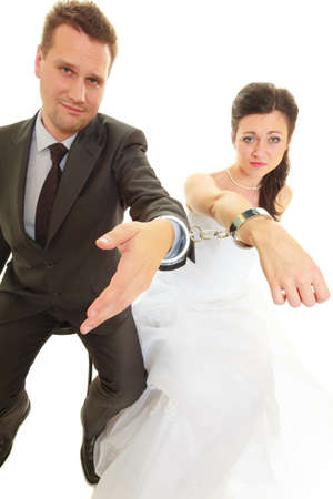 Couple problems, love forever concept. Bride and groom in handcuffs wearing wedding outfits Stock Photo