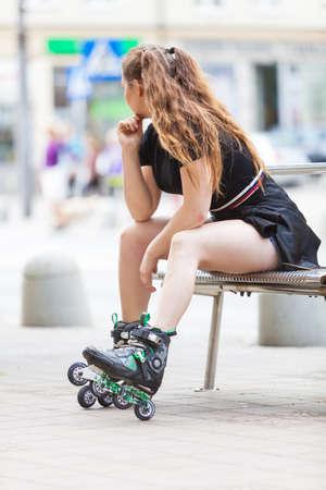 Feliz alegre joven vistiendo patines sentado en la ciudad. Mujer deportiva divirtiéndose durante el verano.